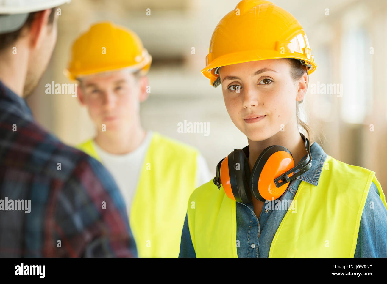 Portrait of woman wearing hard hat and hi vis vest, co-workers in background - Stock Image