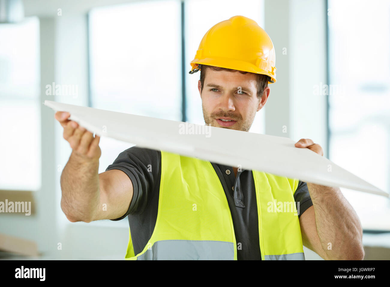 Man wearing hi vis vest, standing in newly constructed space, looking at construction material Stock Photo
