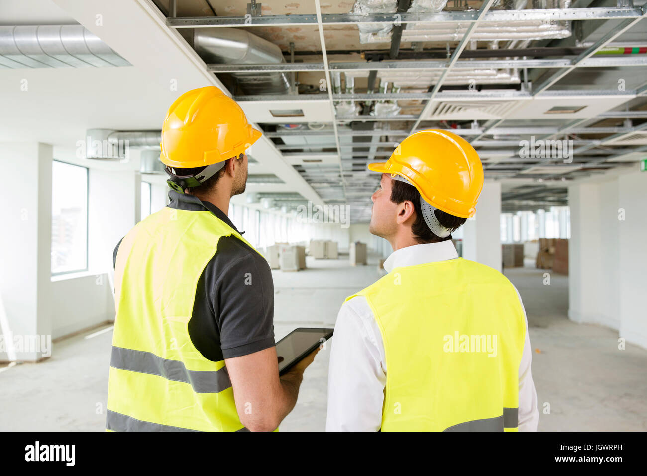 Two men wearing hi vis vest, having discussion in newly constructed office space, rear view - Stock Image