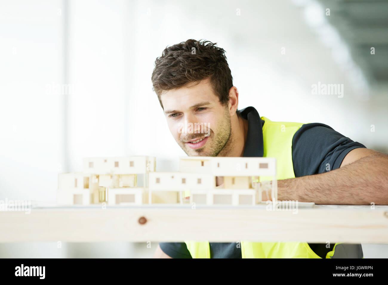 Man wearing hi vis vest, looking at model of building Stock Photo