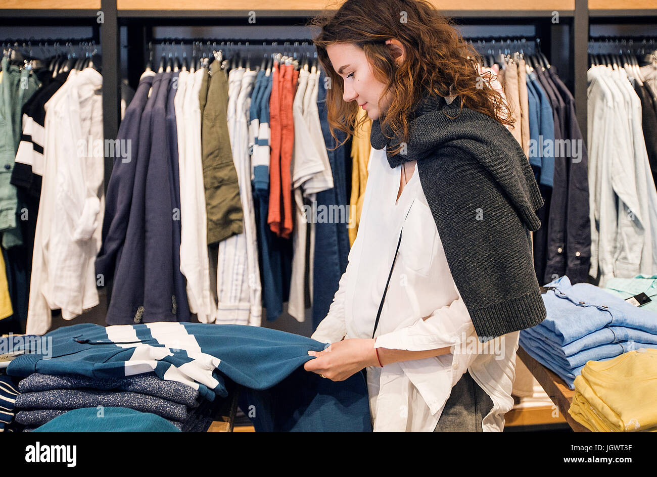 Shopper making decision in clothes shop - Stock Image