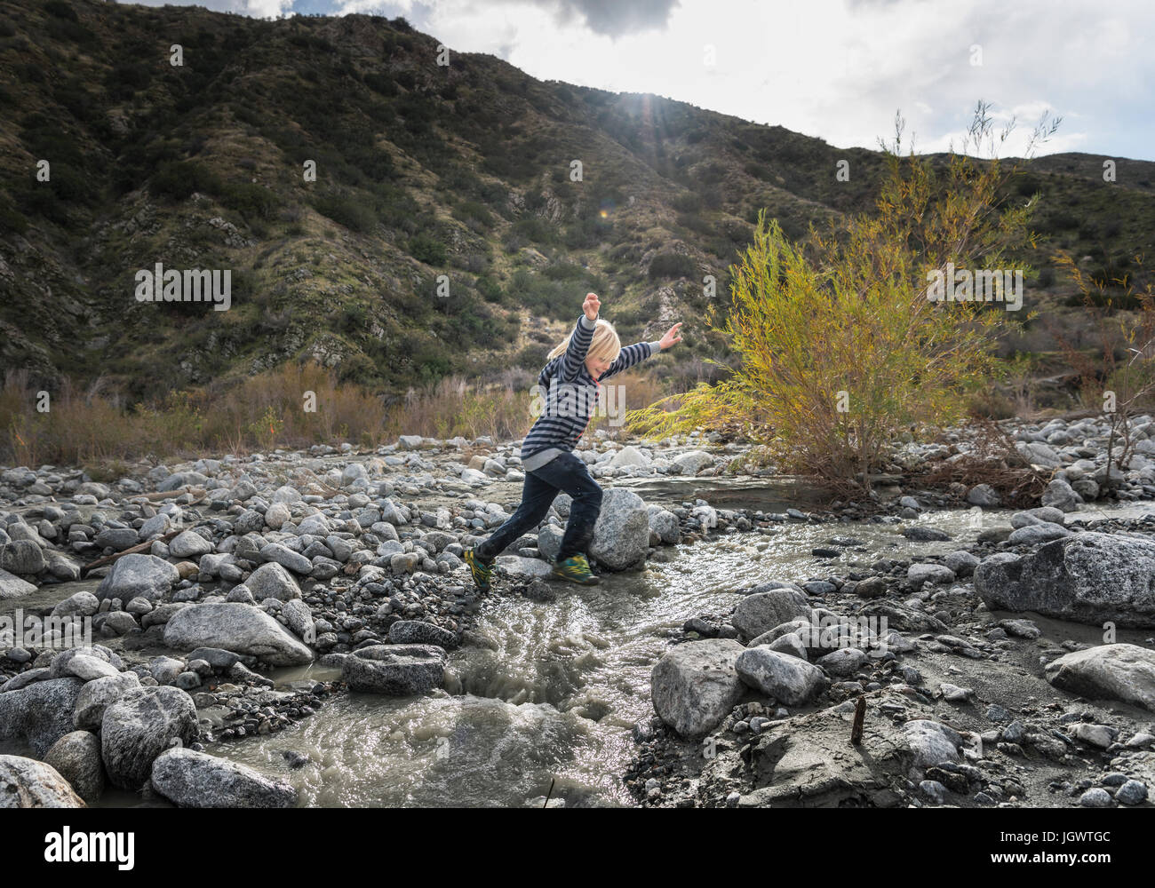 Boy leaping over rocks on riverbed - Stock Image