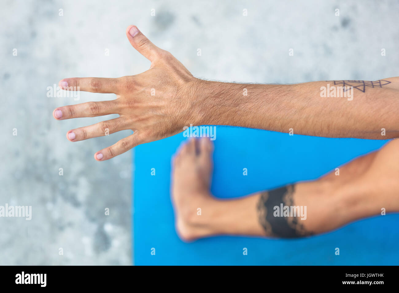 Overhead view of man practicing yoga, standing on yoga mat with arm outstretched - Stock Image