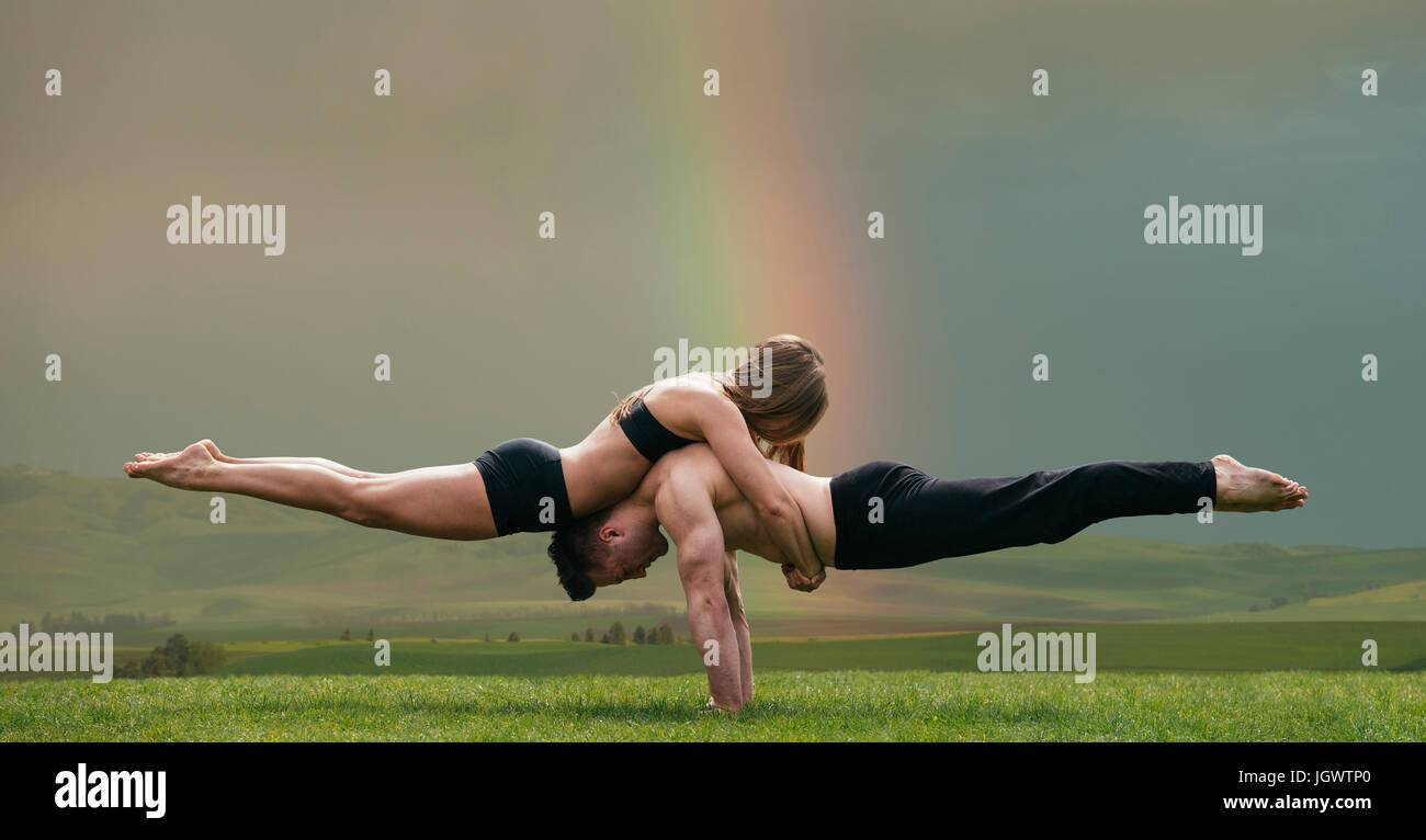 Young woman balancing on top of man in prone position, practicing yoga in front of rainbow - Stock Image