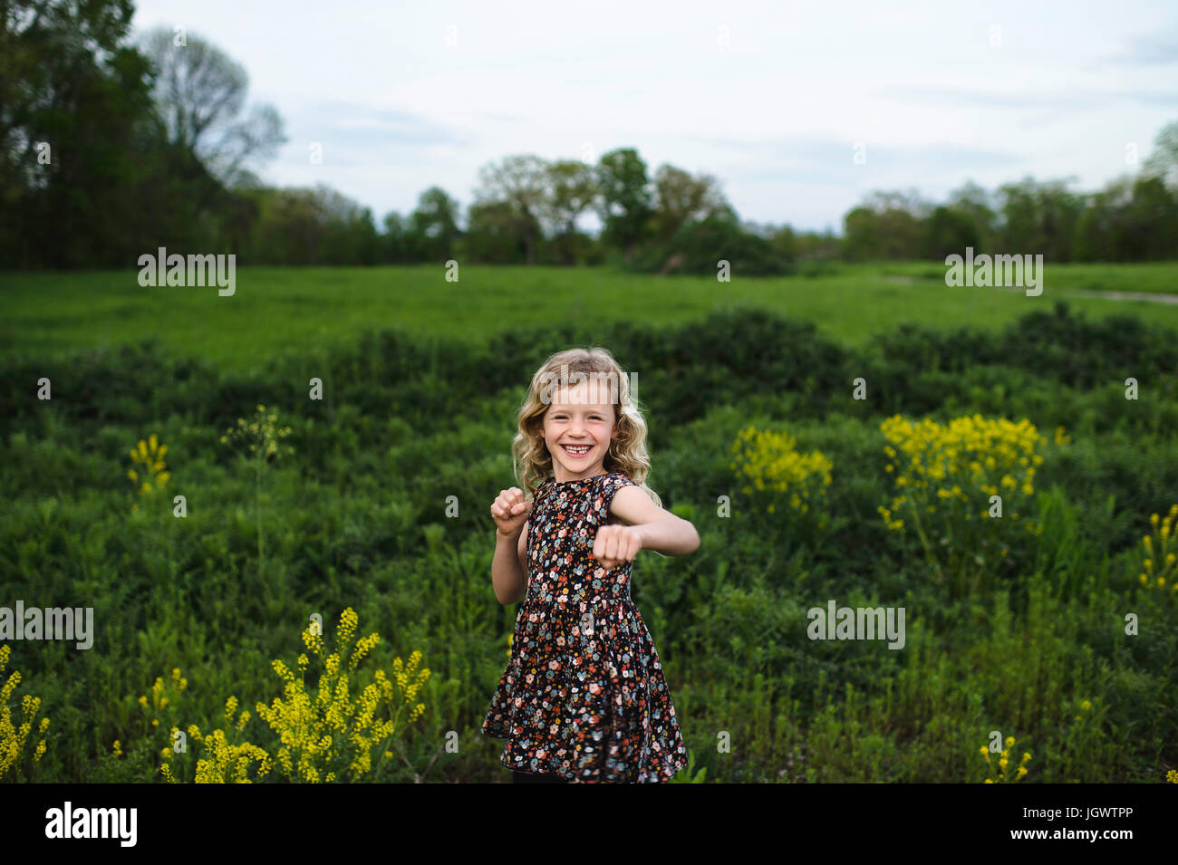 Portrait of girl with wavy blond hair punching in field - Stock Image