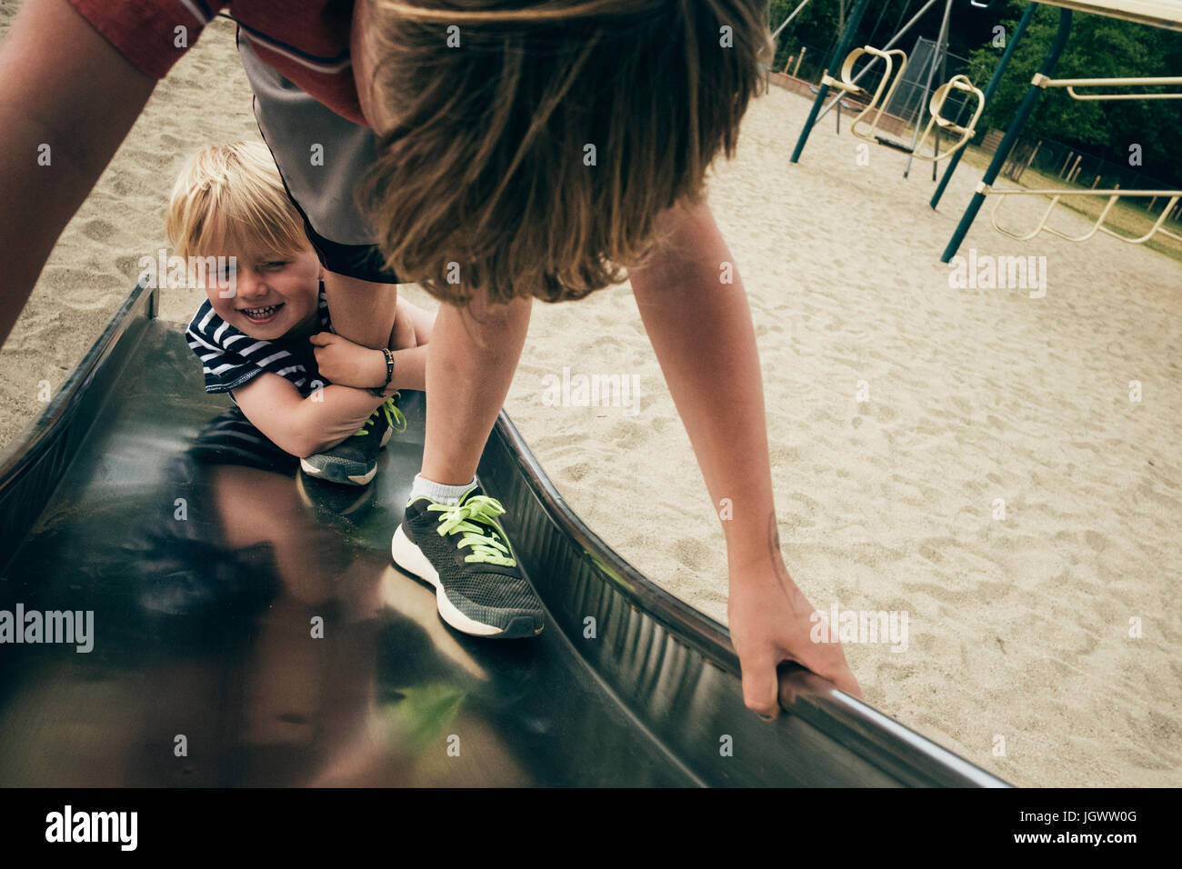 Two boys playing on playground slide, elevated view - Stock Image