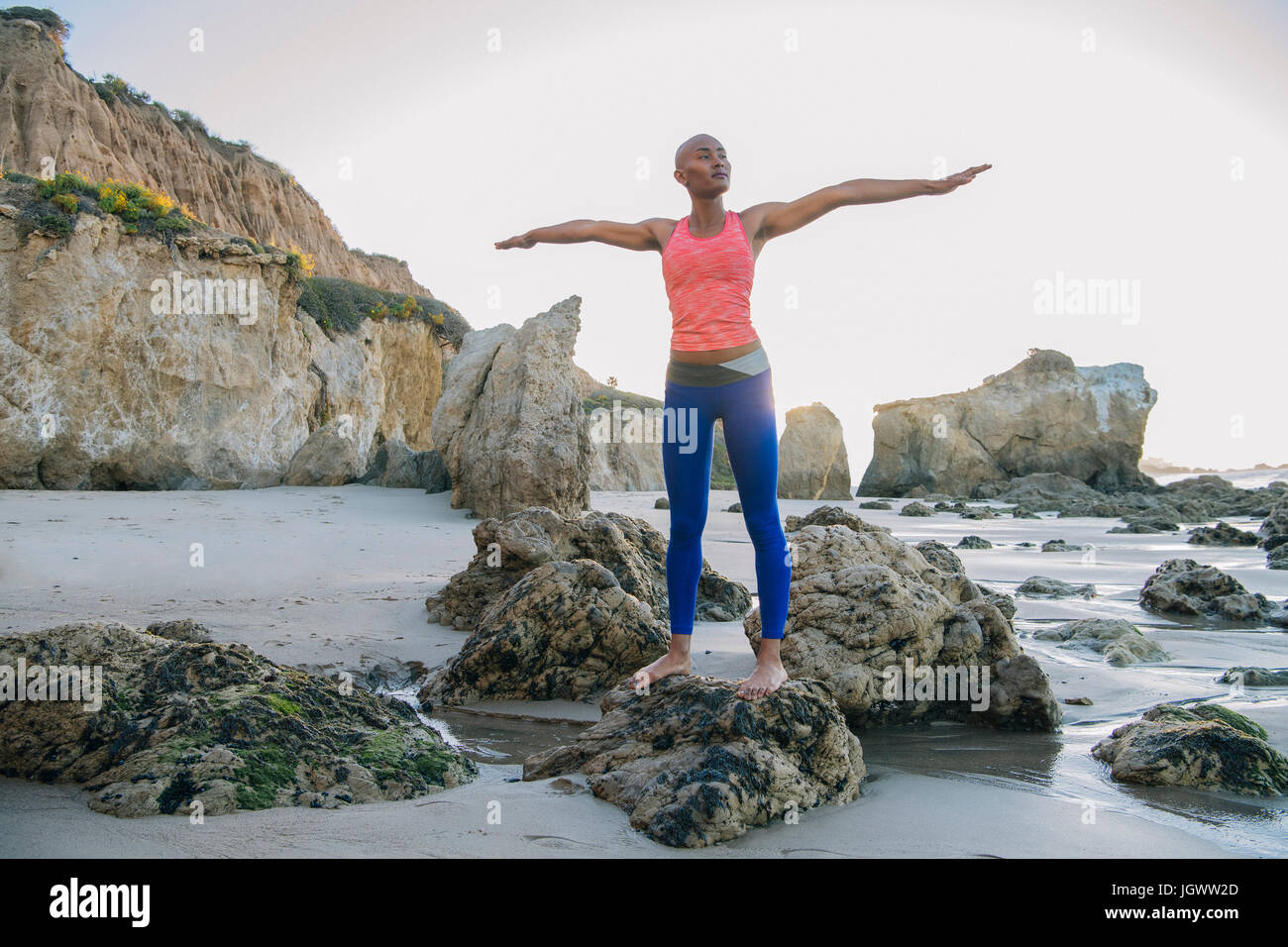 Young woman standing on rocks on beach, arms outstretched - Stock Image