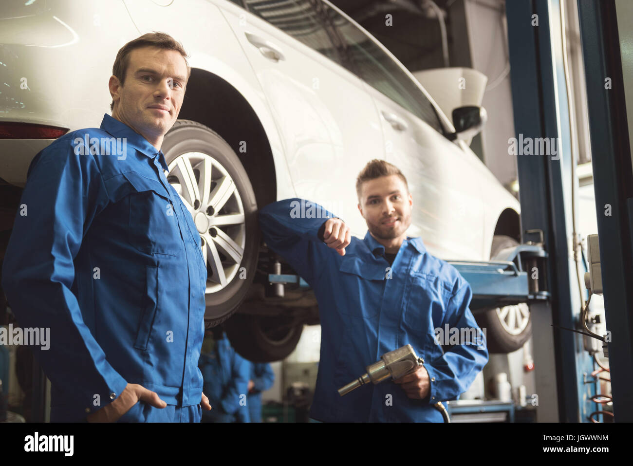 Two colleagues. Industrious serious talented servicemen standing by the auto and deciding what doing next after - Stock Image