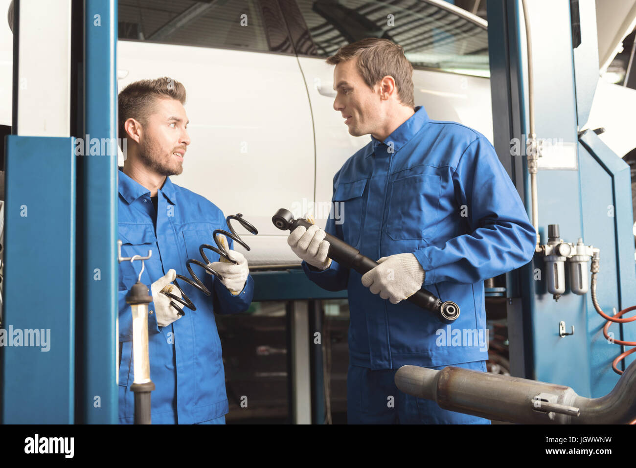 Would you help me. Skillful smart diligent man repairing an auto in the garage and asking his fellow mechanic for - Stock Image