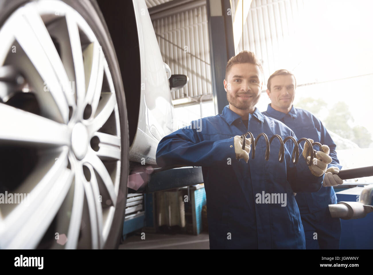 Qualified maintenance. Young pleasant trained mechanic holding a part he intending installing while his colleague - Stock Image