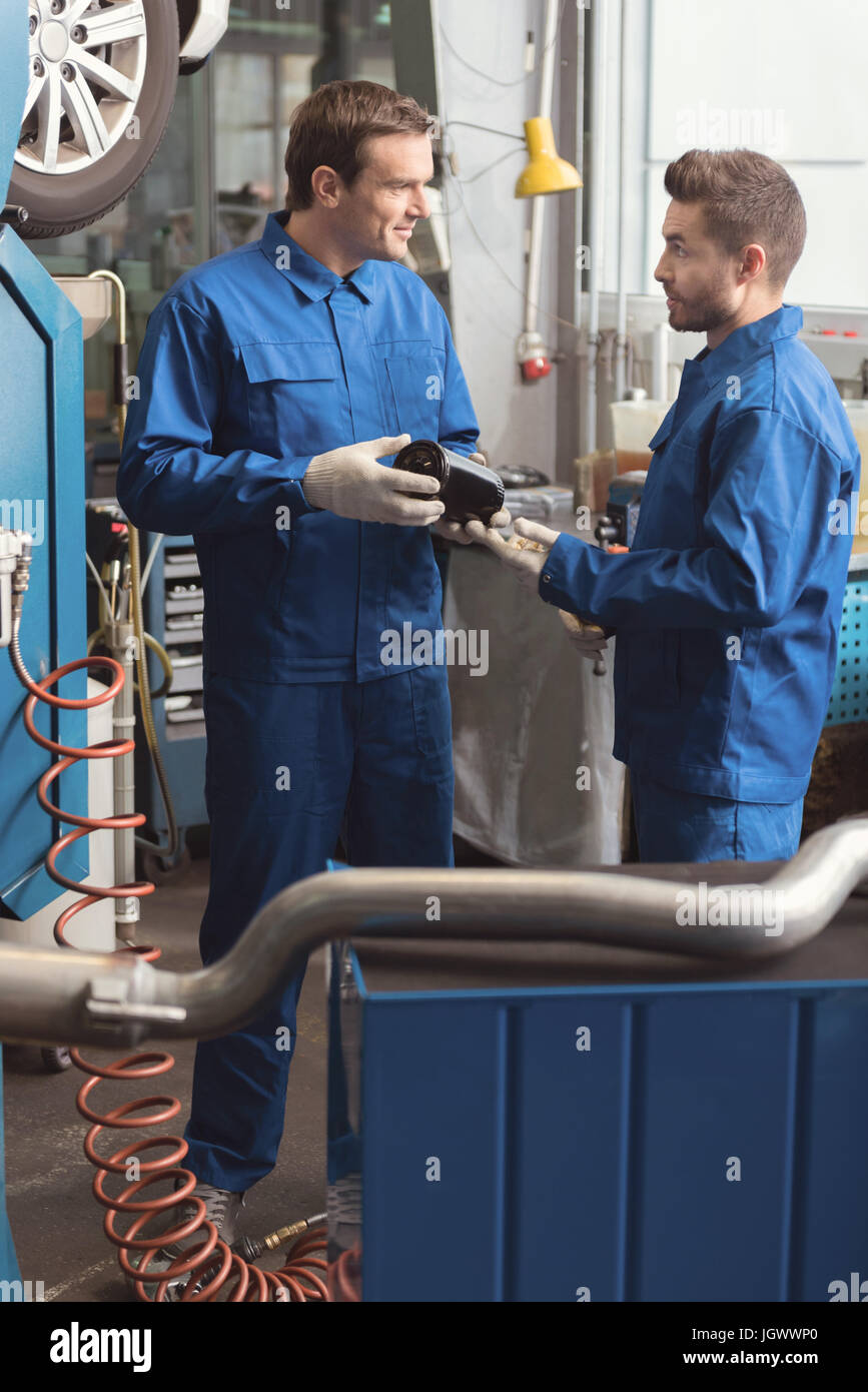 New parts. Diligent competent learned serviceman holding a part of an auto in his hands and hearing what his fellow - Stock Image