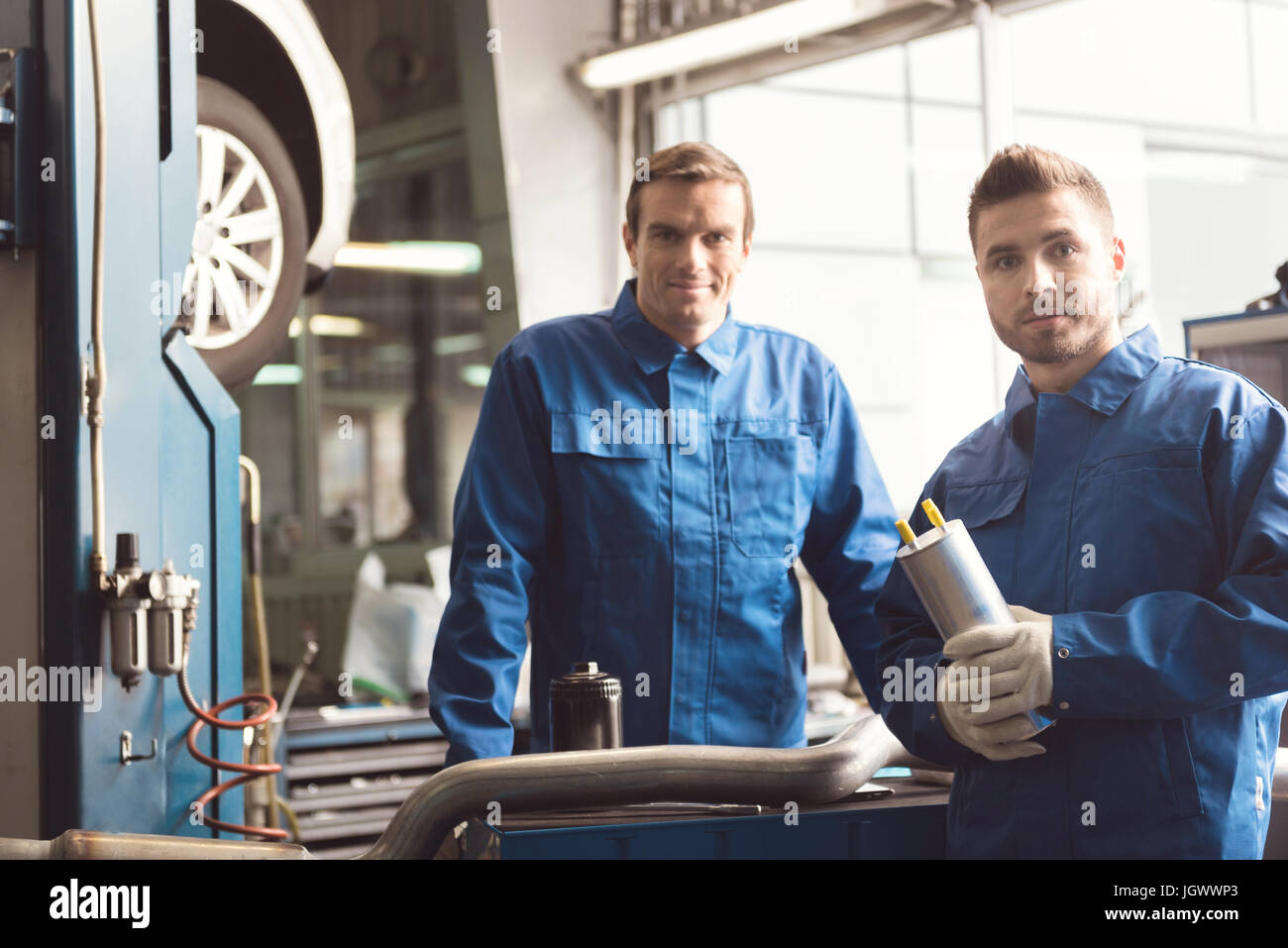 Local team. Hardworking smart industrious servicemen having a little consultation discussing some work issues while - Stock Image