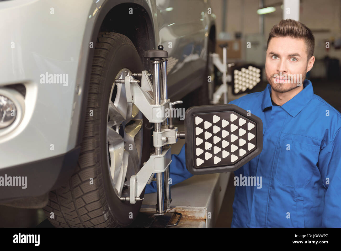 Contemporary technology. Trained attentive skilled worker employing special equipment for setting up wheels of a - Stock Image