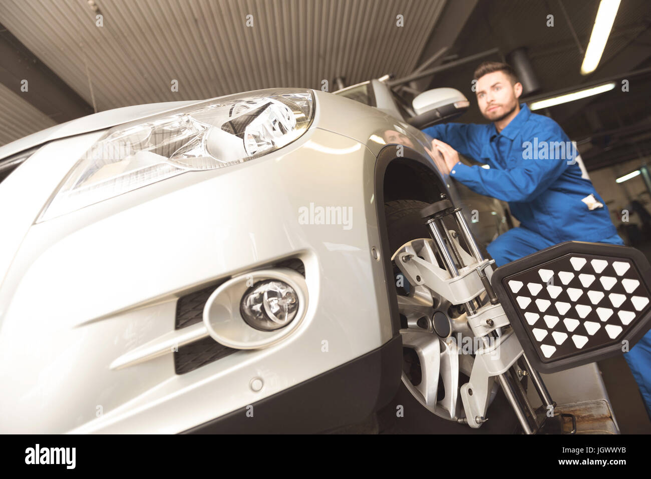 Up to date technologies. Successful determined car expert employing special tools for fixating autos wheels while - Stock Image