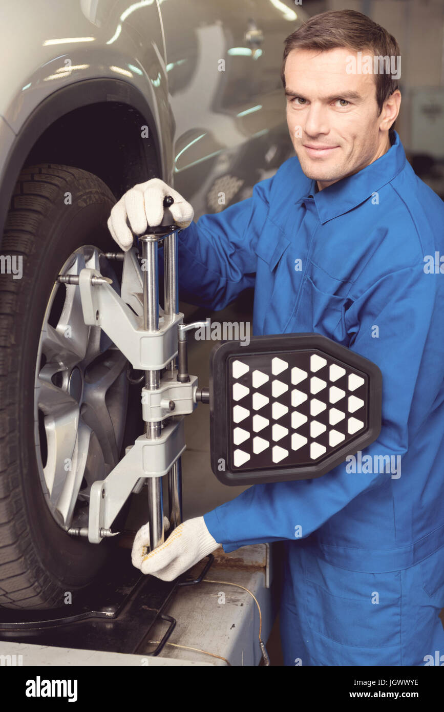 Best tinker in town. Handsome trustworthy excellent serviceman employing special equipment for doing a checkup on - Stock Image
