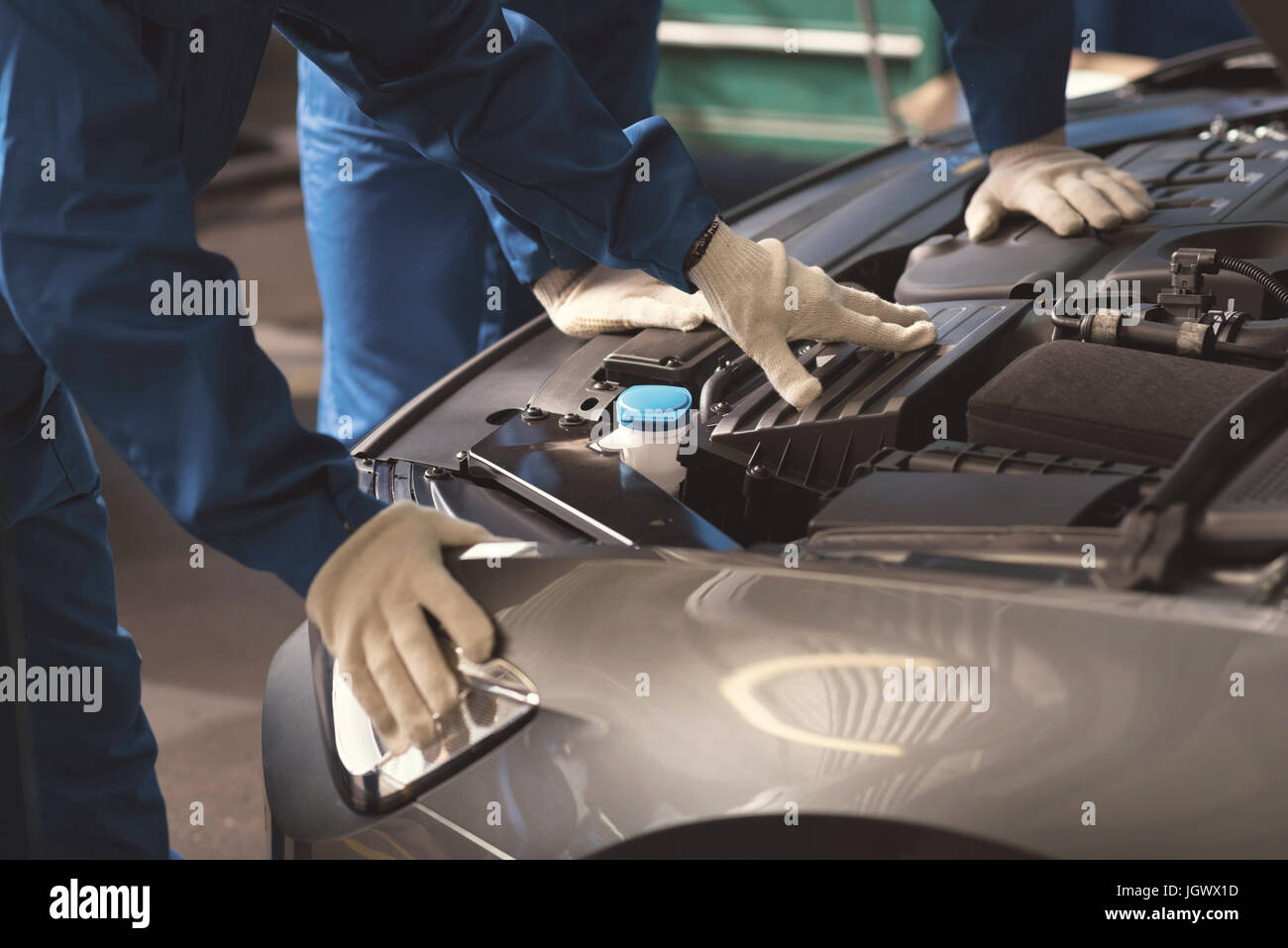 Careful study. Fine successful local experts performing a checkup on clients automobile and making sure all mechanisms - Stock Image