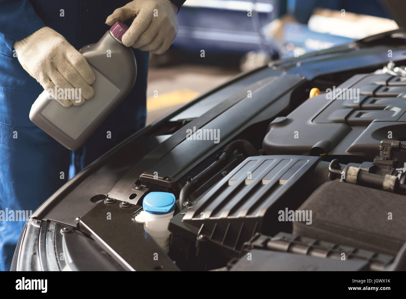Professional care. Competent successful local tinker performing a maintenance procedure and using specific fluid - Stock Image