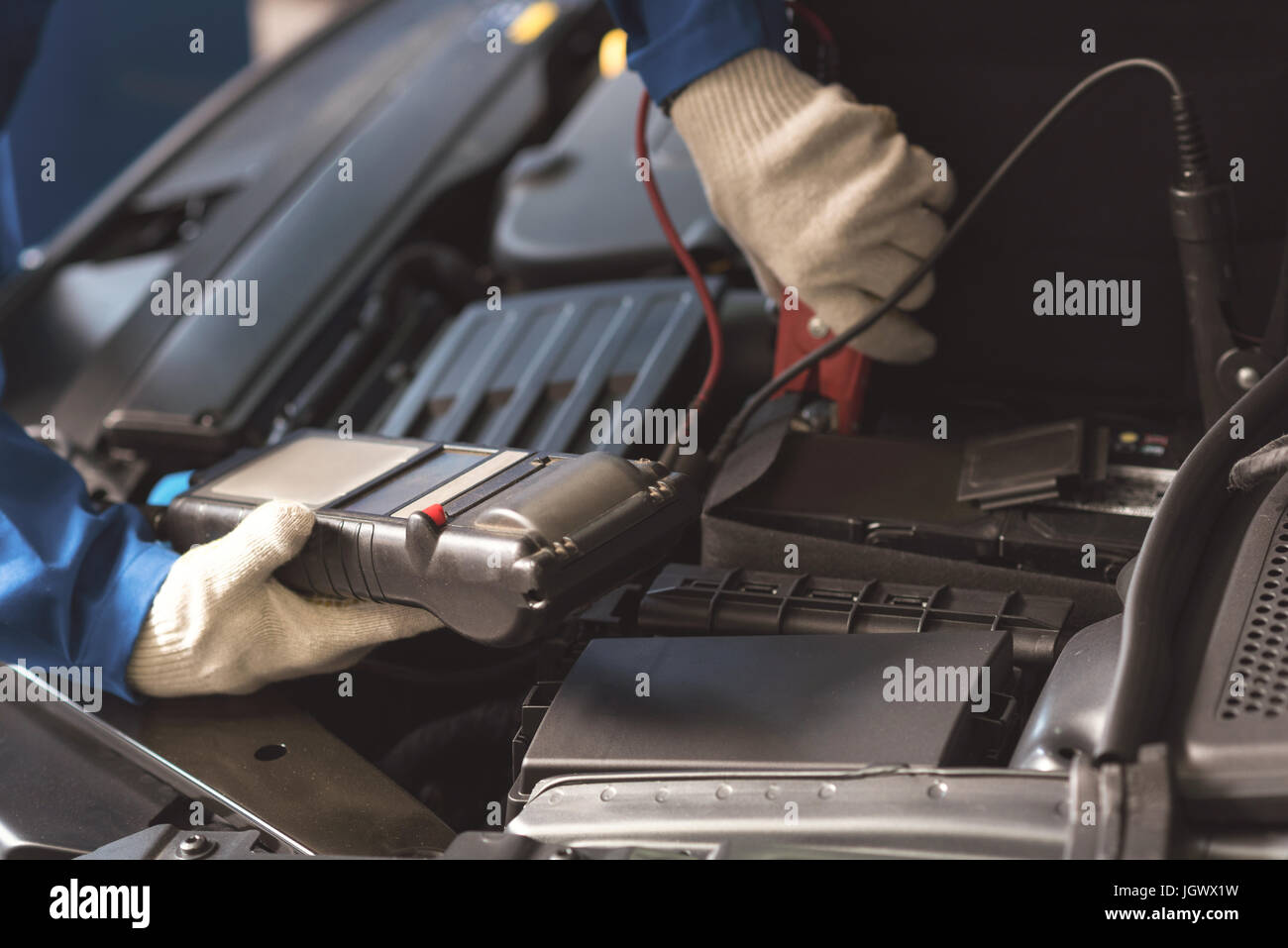 Plug in wires. Talented skillful trained serviceman employing special indicator for measuring something while conducting - Stock Image