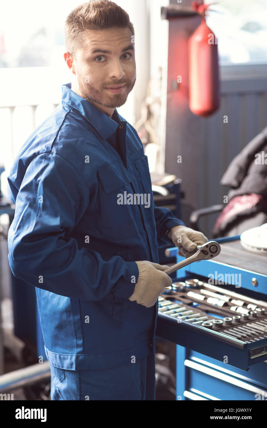 Mens kingdom. Good handsome qualified serviceman standing by the tool box and choosing which equipment he needing - Stock Image