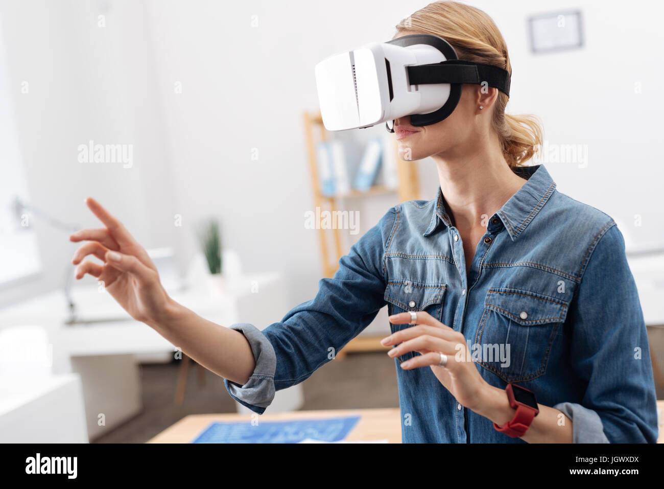 Simulating sensations. Pleasant interested curious woman taking part in the tech experiment and testing visual reality - Stock Image