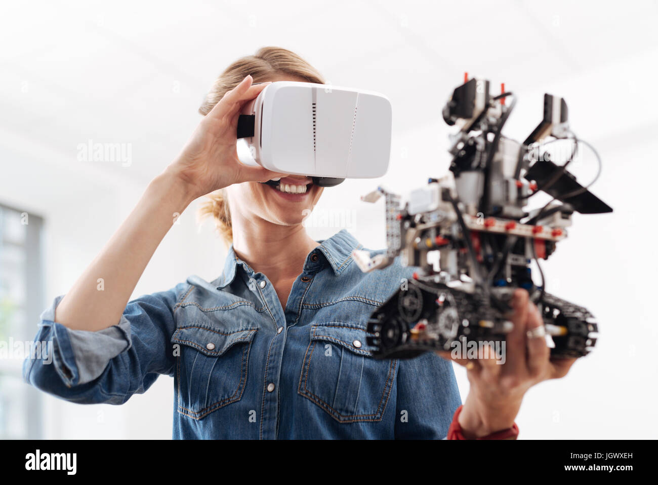 Enjoying new sensations. Smiling glad pleasant woman using visual reality headset while holding little smart robot - Stock Image