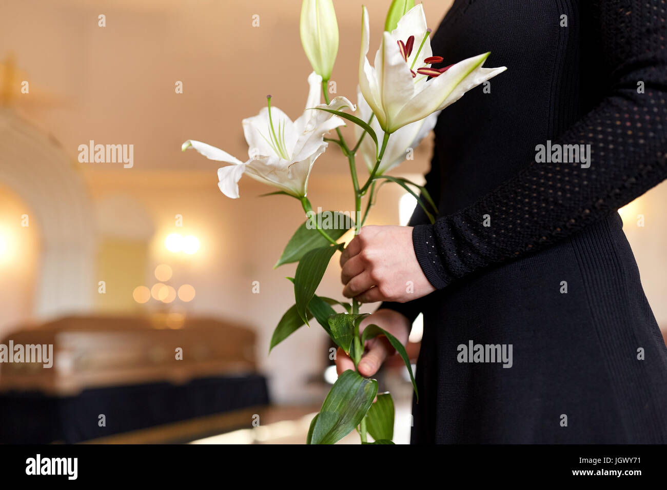 Close Up Of Woman With Lily Flowers At Funeral Stock Photo
