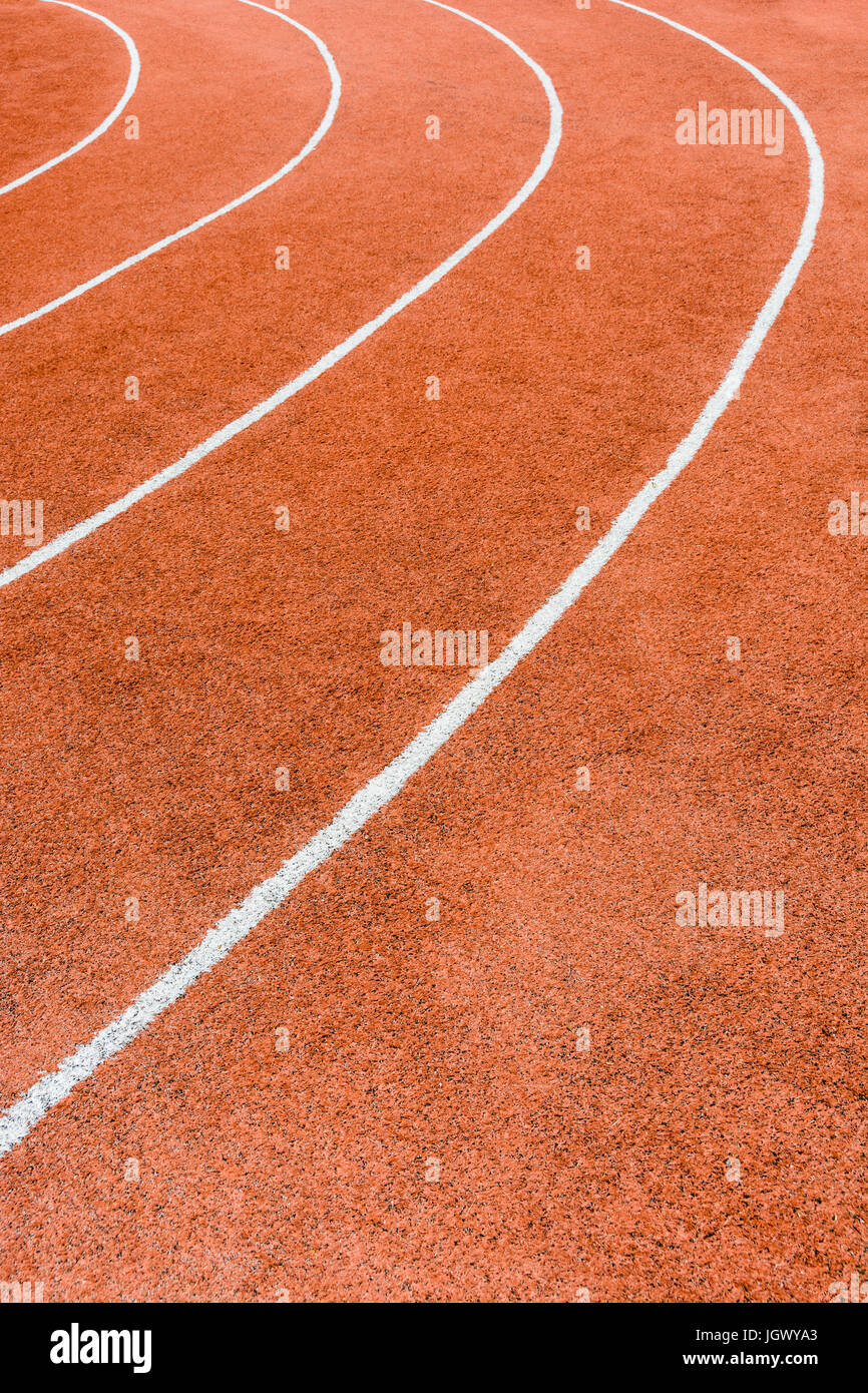 Close up view of a red athletics track with white lines defining the lanes. - Stock Image