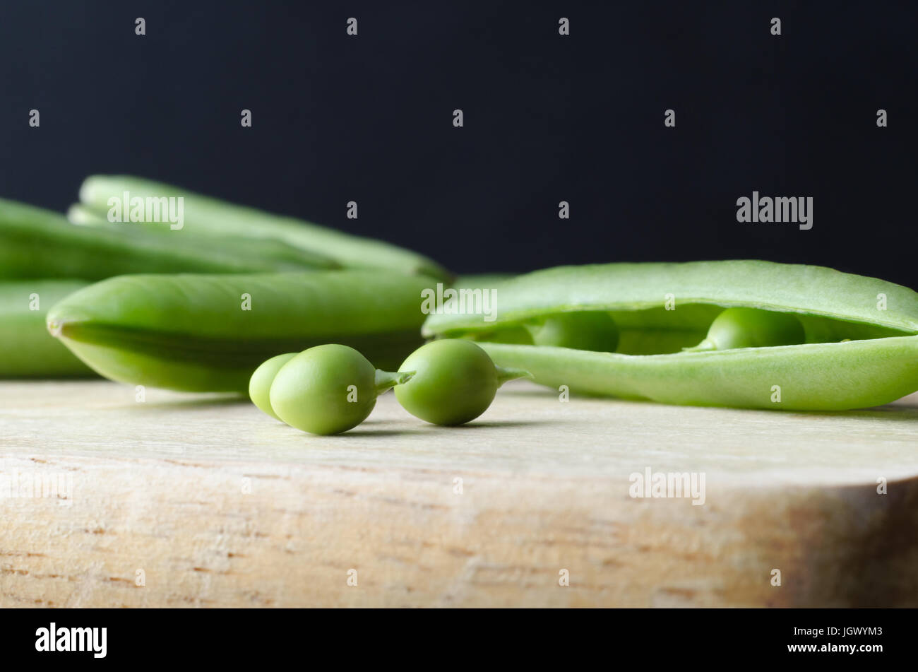 Close up (macro) of three peas with stalks intact on wooden chopping board. The opened pod from which they were - Stock Image