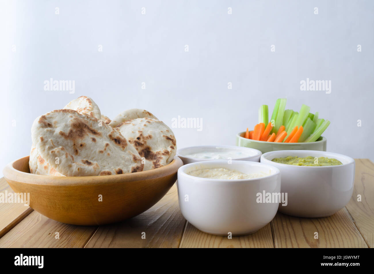 A selection of dips on a wood plank table, with bowls of  pitta bread and crudites.  Includes; hummus; guacamole; - Stock Image