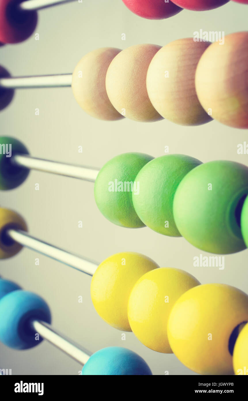 Close up of rows of abacus beads in bright colours,  angled and leading away into soft focus. Cross processed to - Stock Image