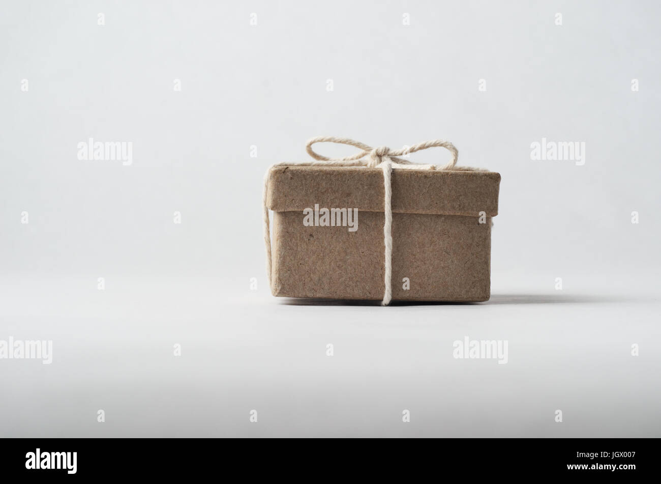 Eye level shot of a simply packaged brown cardboard box with lid, tied to a bow with string.  Off white background. - Stock Image
