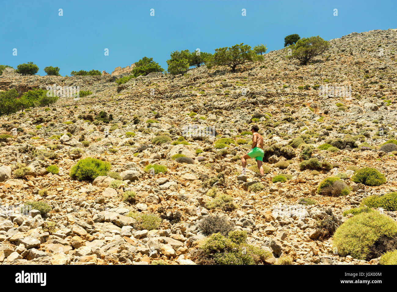 Man in brightly coloured shorts ascending a rocky hillside in hot weather to reach a castle at the top of the hill. - Stock Image