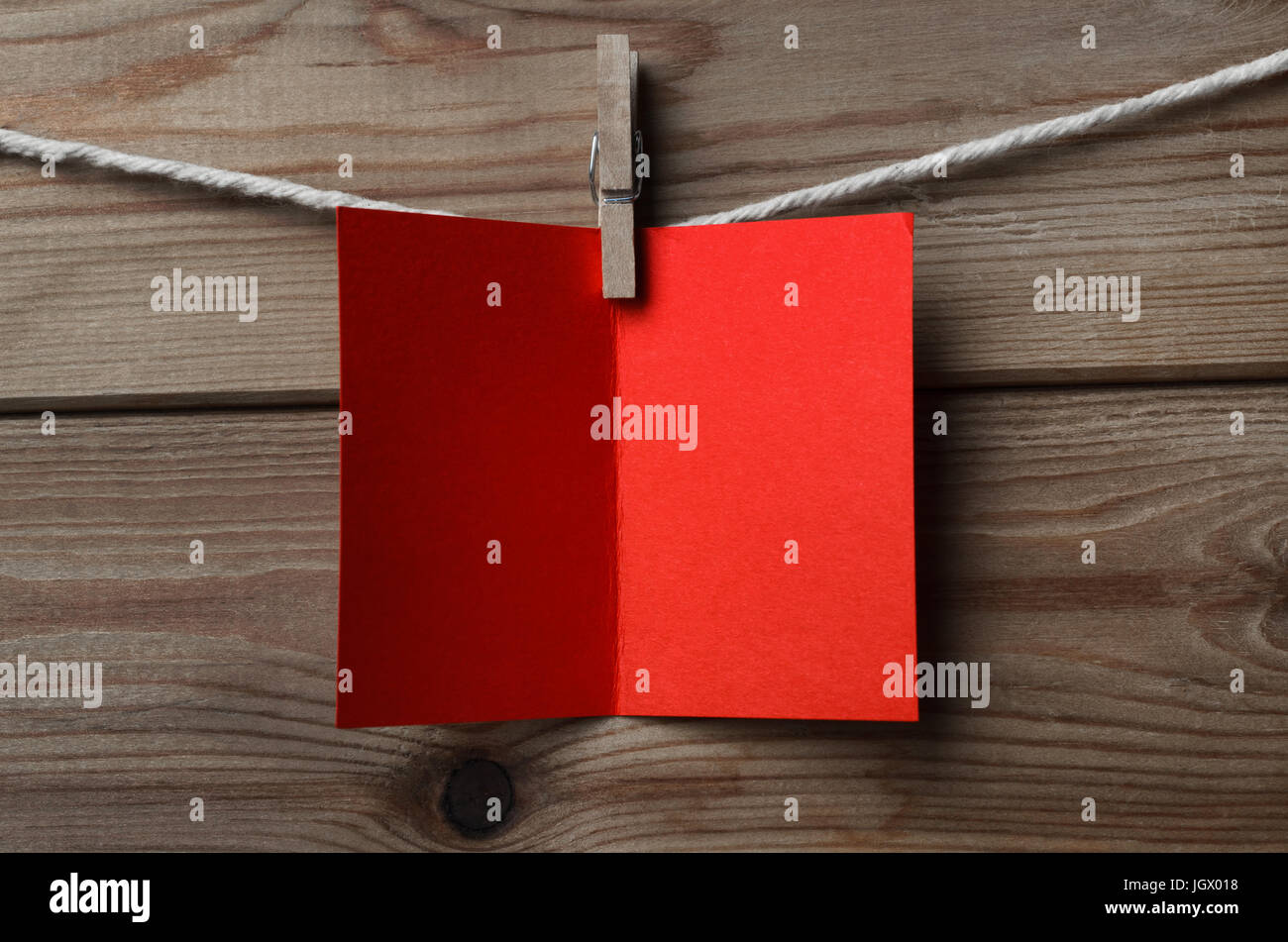 An opened, blank red greeting or Christmas card, pegged on to string against wood plank background - Stock Image