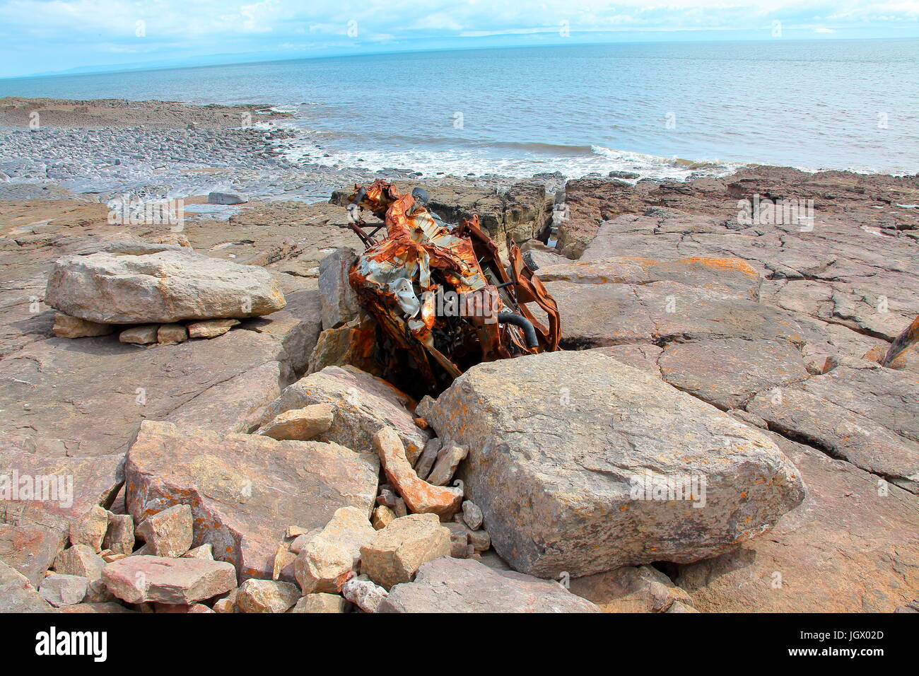 The wreckage of a Beach Buggy firmly wedged into a crevice in the beach rocks just above the high water mark on - Stock Image