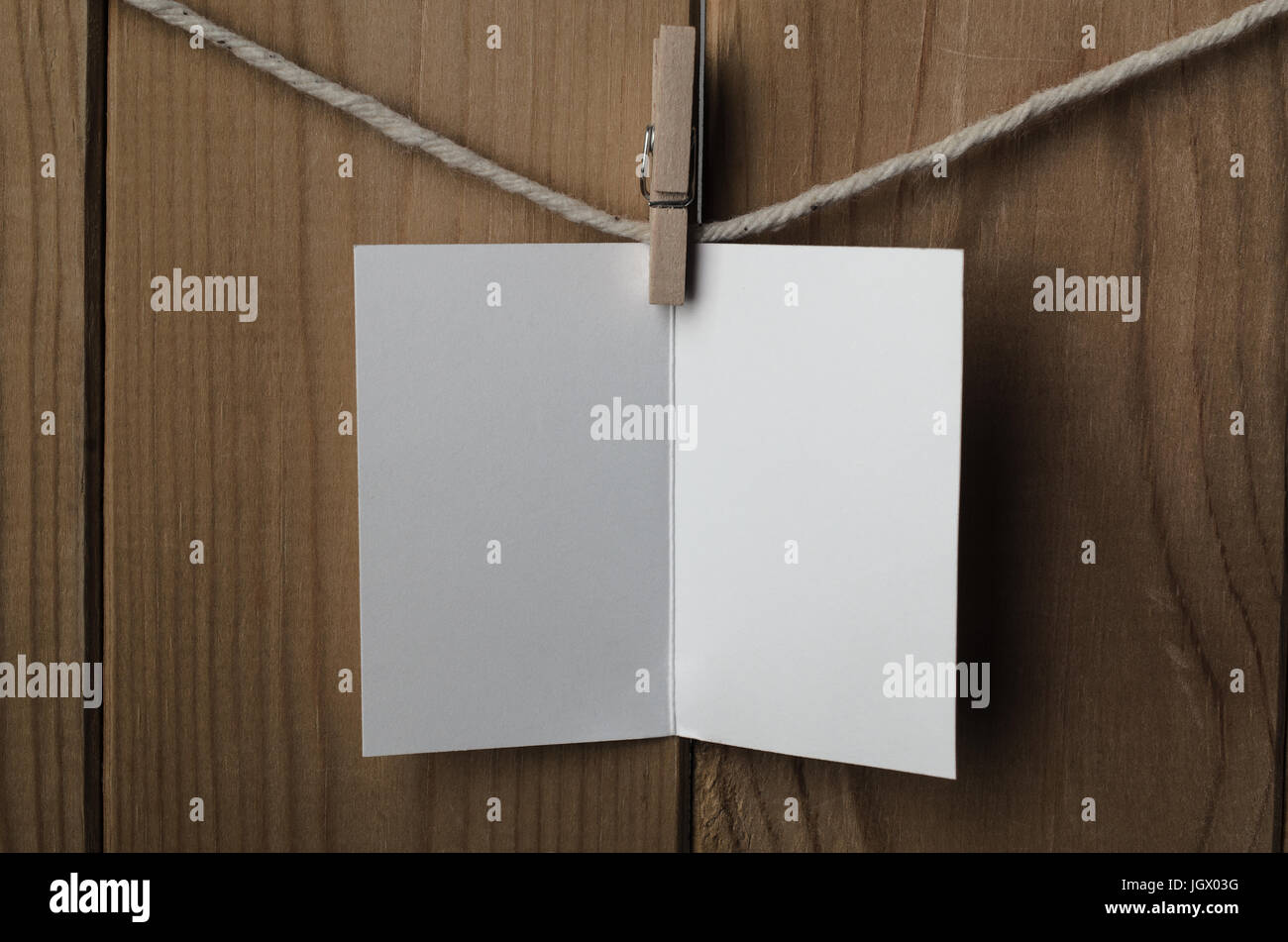 An opened, blank, plain white greetings or Christmas card, pegged to string against wood plank background. - Stock Image