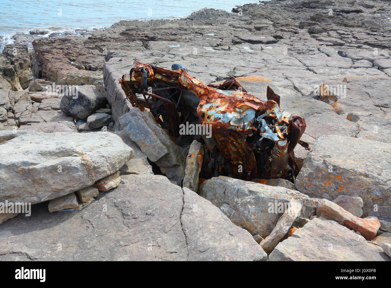 A Beach buggy totally wedged into a rock crevice and held tight by huge boulders just above the high water mark - Stock Image