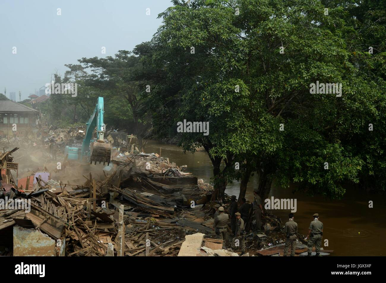 Jakarta, Indonesia. 11th July, 2017. An excavator destroys houses in the evicted area of the Bukit Duri neighbourhood - Stock Image