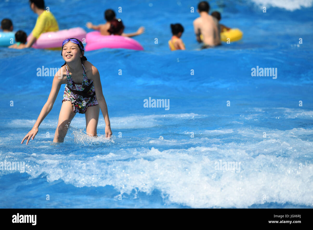 Chongqing, China. 11th Jul, 2017. A girl played in water to keep cool in a water park in Chongqing, July 11, 2017. - Stock Image