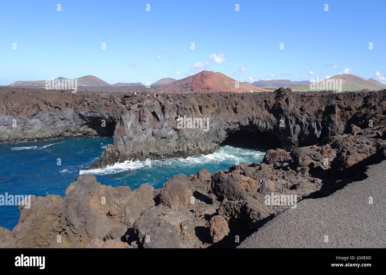 Die Felskueste Los Hervideros, dahinter die Feuerberge, Montanas del Fuego, El Golfo, Lanzarote, Kanarische Inseln, - Stock Image