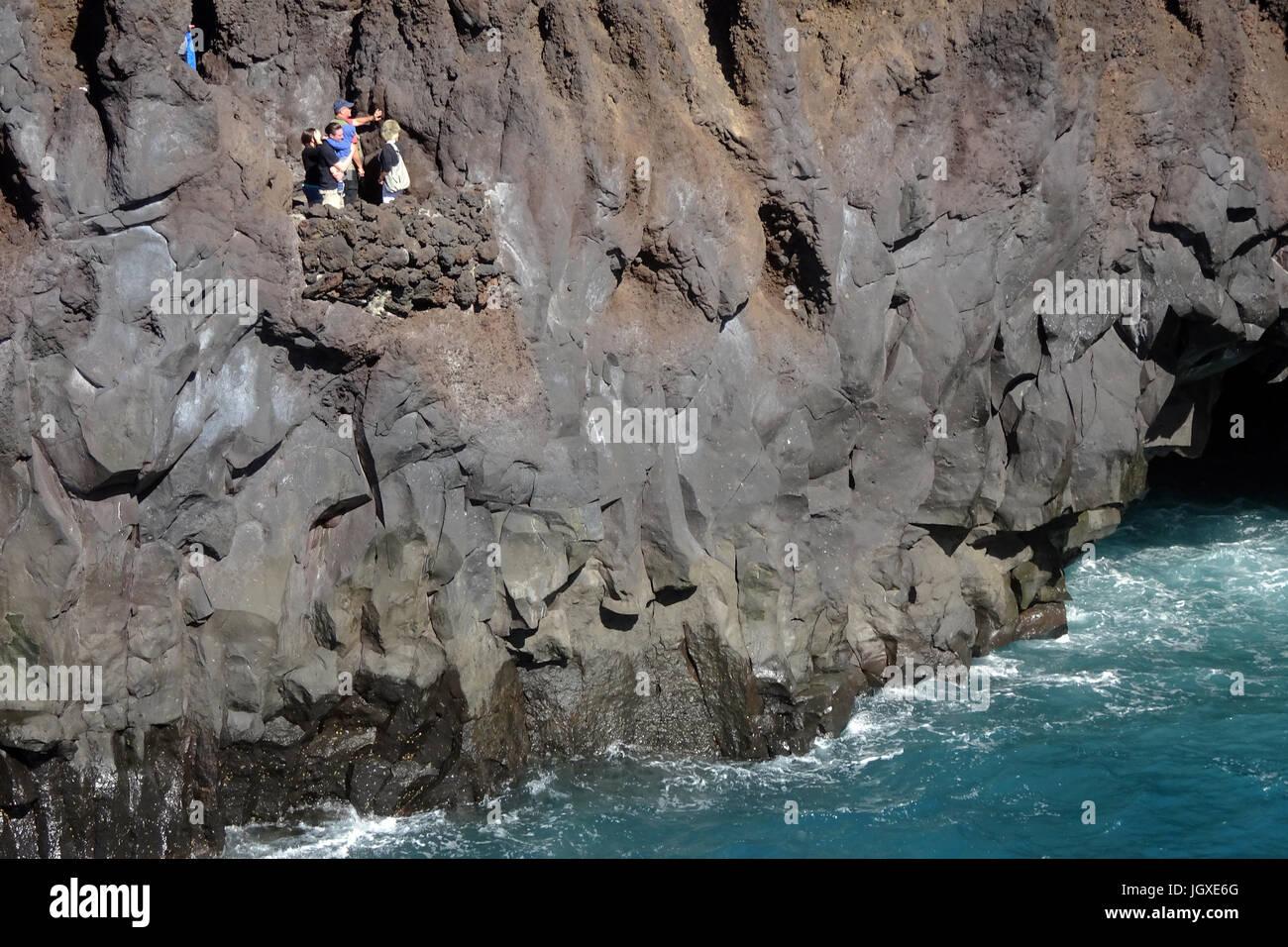 Touristen auf einer kleinen Aussichtsplattfon an der Felskueste Los Hervideros, El Golfo, Lanzarote, Kanarische - Stock Image