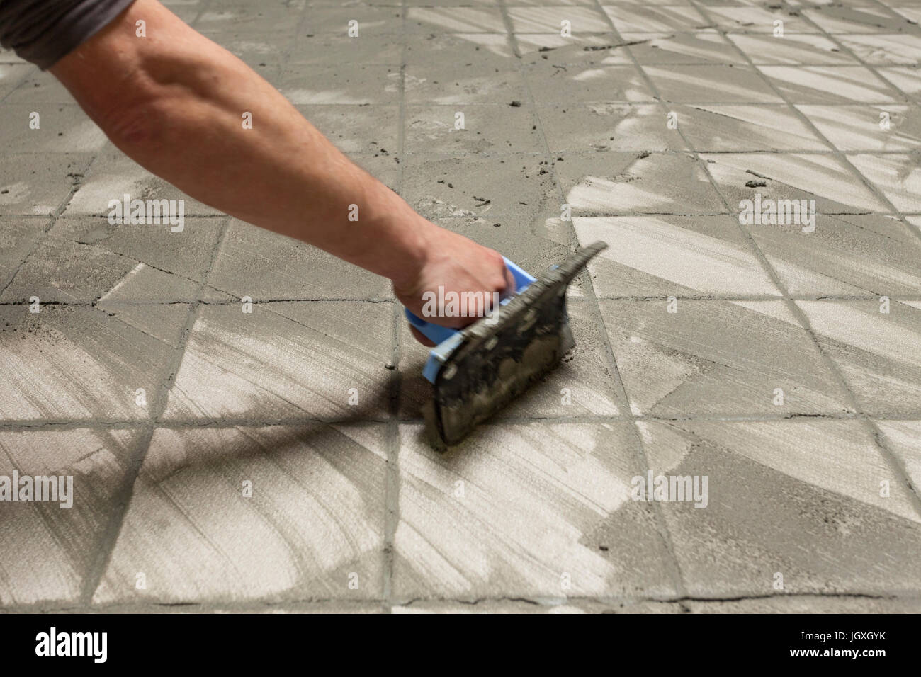Masterfully Gluing Ceramic Tiles In An Industrial Room Stock Photo