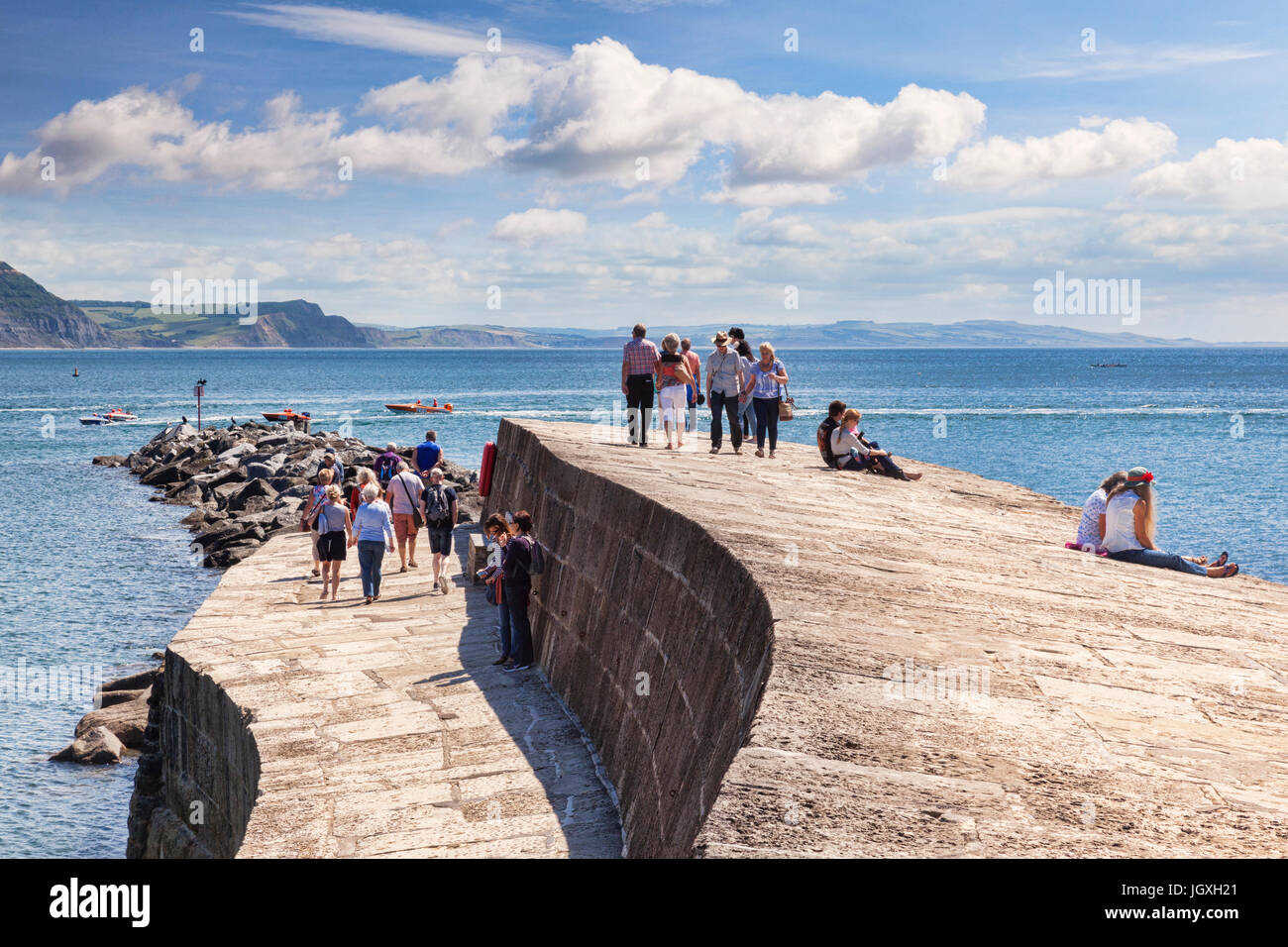 1 July 2017: Lyme Regis, Dorset, England, UK - Visitors enjoying the good weather on The Cobb. - Stock Image