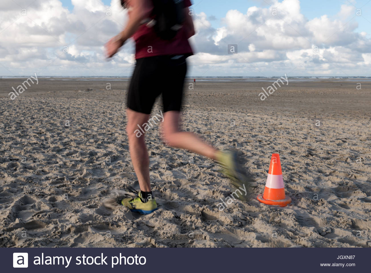 Traffic cone on sand beach with many footsteps man running Stock Photo