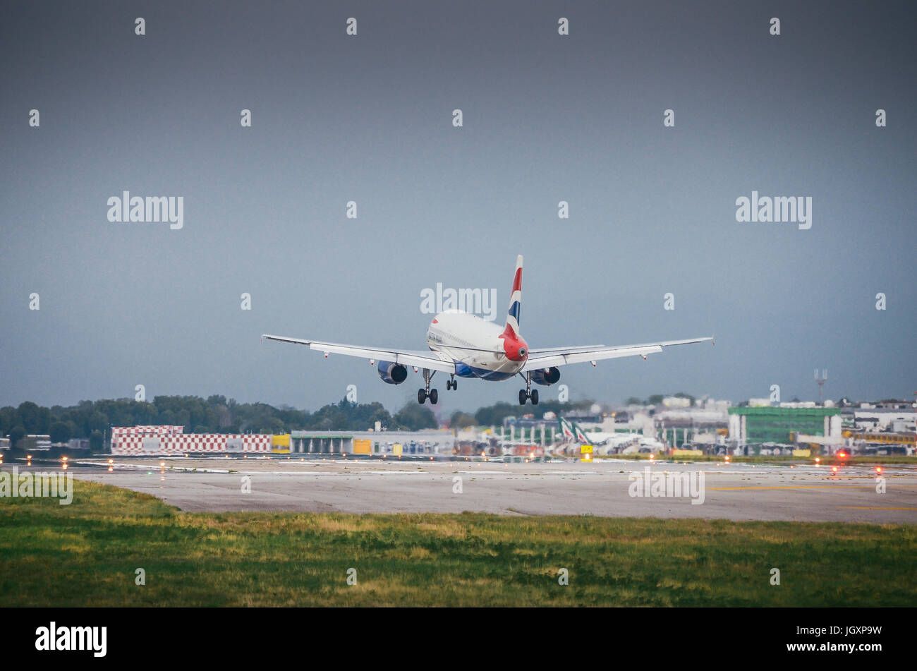 A British Airways commercial airplane lands at Milan's Linate airport - Stock Image
