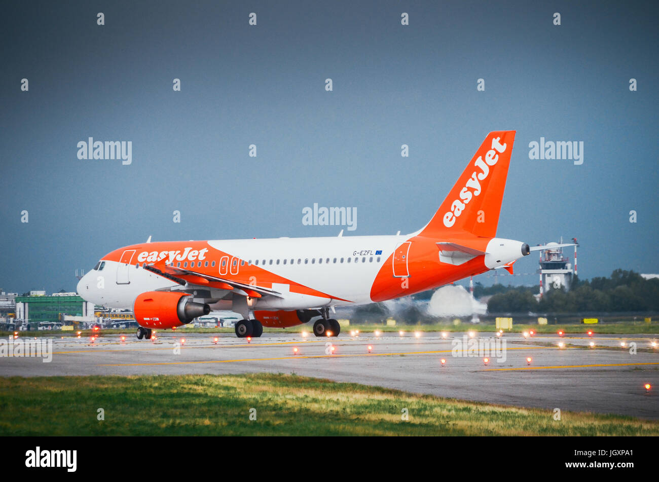 An Easyjet commercial airplane lands at Milan's Linate airport - Stock Image