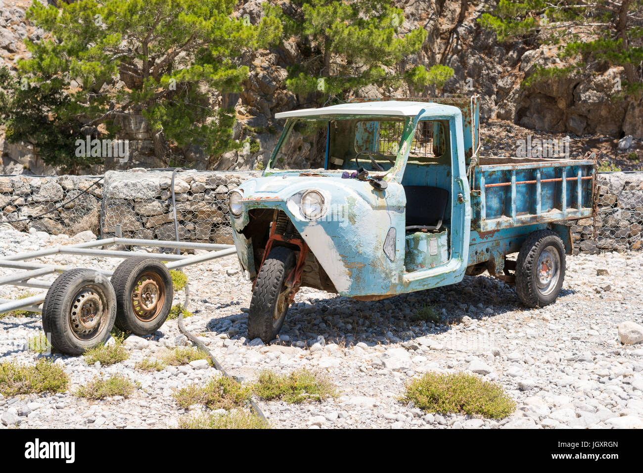 Three wheeled vehicle looking in need of some restoration but still in use in agricultural Greece. - Stock Image