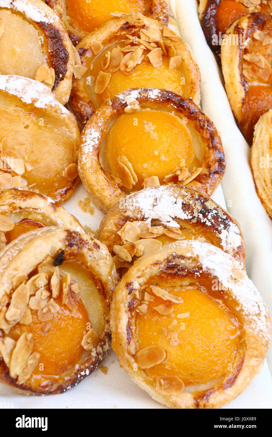 Apricot mini tarts with almond slices, seen at a street fair celebrating Bastille Day in NYC - Stock Image