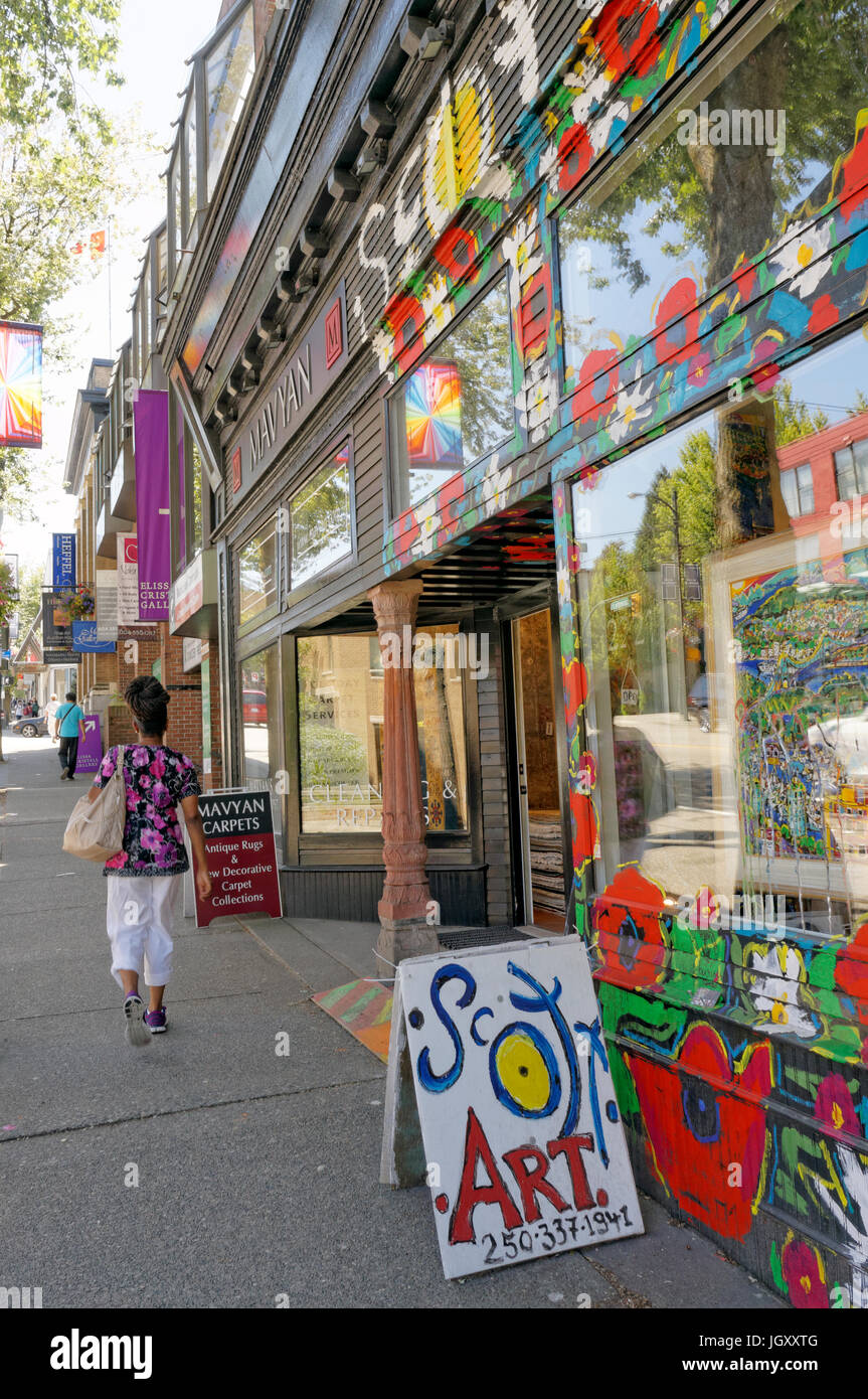 Woman walking past a colorful painted facade of an art store on gallery row, South Granville Street, Vancouver, - Stock Image