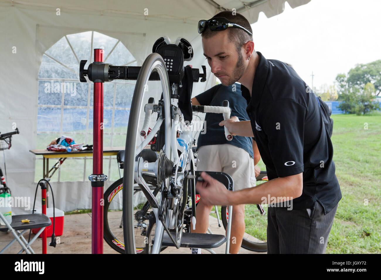 Bicycle mechanic fixing wheel with bicycle mounted on bike mount - USA - Stock Image