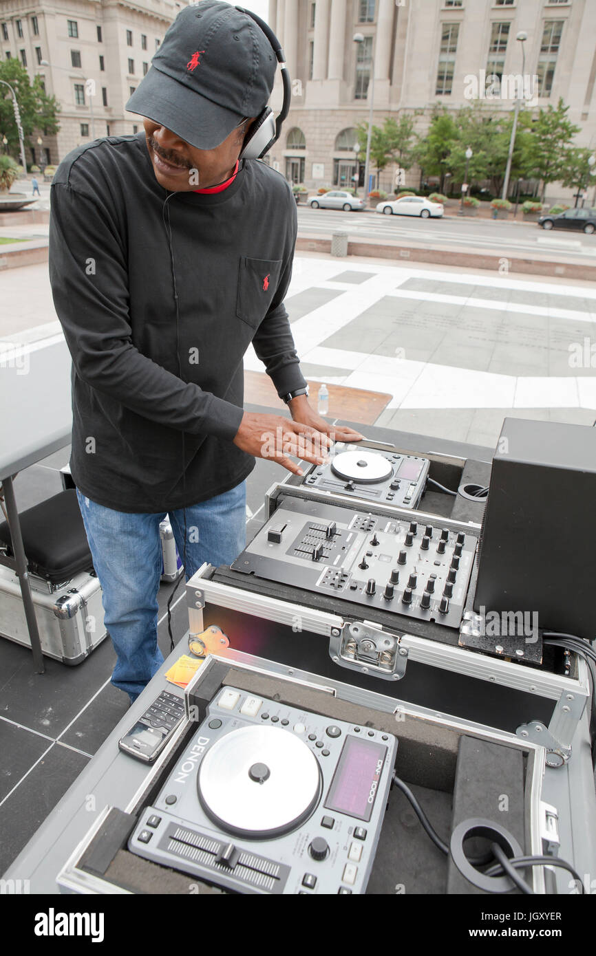 DJ using a music mixer at an outdoor event - USA - Stock Image